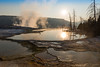 The rising sun backlights the still pools and the travertine terraces at Mammoth Hot Springs in Yellowstone National Park in Wyoming.
