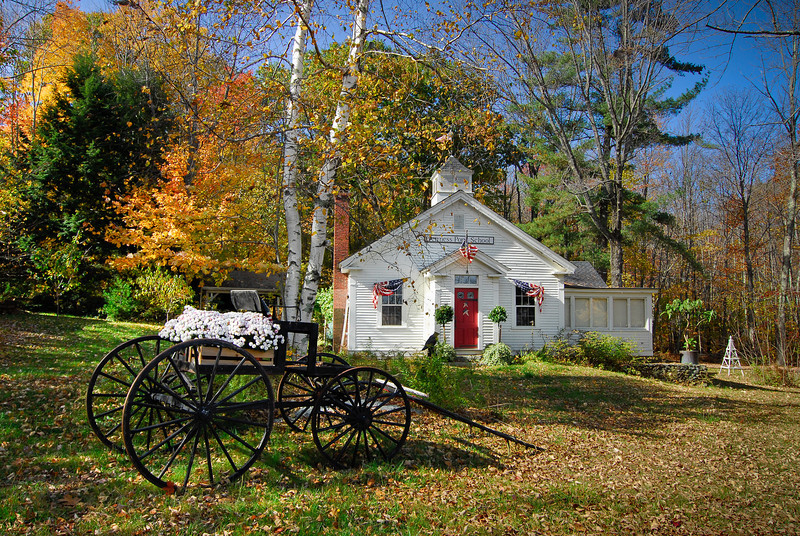 Jenness Pond School, circa 1793, with American flag and patriotic buntings, carriage with mums, and fall color, Northwood, NH.