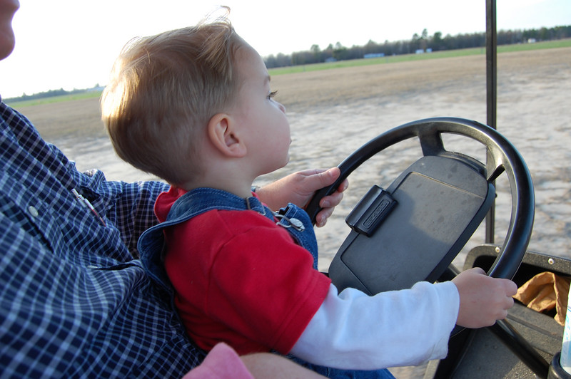 Connor driving the golfcart with Genddaddy out on the farm in Oates.