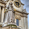 Queen Anne's Statue<br /> There us a group of white marble figures that stand in front of St. Paul's Cathedral in London. This group with Queen Anne, surrounded below by figures representing England, France, Ireland, and the North American Colonies is an exact replica of a group originally created in 1712.<br />  <br /> The original creation sat for many years in a disgraceful state of neglect, with the Queen's nose chipped off, and several legs and arms missing. The whole composition was cleared away, and an entirely new one put in its place in the late 1800s. The old lady is starting to show some wear again, but she still stands proudly above the four other  figures.
