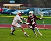 Auburn Maroons Dan Entenmann (18) being defended by Baldwinsville Bees Matthew Dickman (24) in Section III Boys Lacrosse action at the Pelcher-Arcaro Stadium in Baldwinsville, New York on Monday, April 27, 2015..  Auburn won 14-10.
