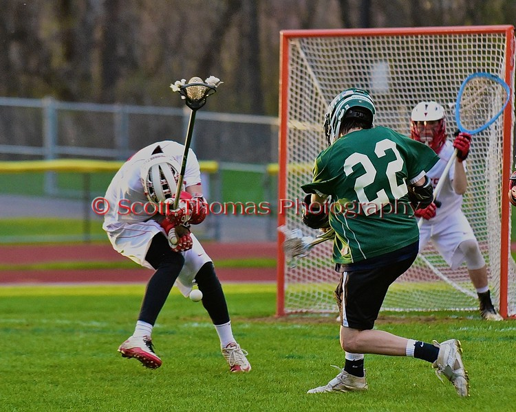 Fayetteville-Manlius Hornets Erik Badger's (22) shot is blocked by a Baldwinsville Bees defender in Section III Boys Lacrosse action at the Pelcher-Arcaro Stadium in Baldwinsville, New York on Friday, May 1, 2015.  Baldwinsville won 11-9.