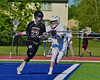 Syracuse Cougars Jack Kane (23) being defended by Auburn Maroons Reed Chronis (14) in Section III Boys Lacrosse Semi-Final game at the Michael J. Bragman Stadium in Cicero, New York on Saturday, May 23, 2015.  Auburn won 14-6.