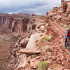 Female mountain biker cycles the cliff-edge Amasa Back trail, Moab, Utah, USA.