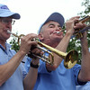 Former town moderator Dennis McHugh, left, and his brother Peter McHugh, center, play trumpet with the Chelmsford Community Band in the Chelmsford 4th of July parade. (SUN/Julia Malakie)
