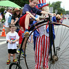 Uncle Sam invites Colin Sexton, 8, of Chelmsford, to take a ride on his bicycle. (SUN/Julia Malakie)