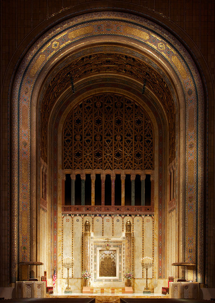 """Temple Emanu-El Ark, Mosaic by  Hildreth Meière <br><br> From a pdf file from the <a href=""""http://www.emanuelnyc.org/simple.php/about_tour"""">Temple Emanu-El website:</a>  <br><br> """"As in the tradition, Temple Emanu-El's ark is located on the eastern wall of the sanctuary, facing Jerusalem. Emanu-El's ark was designed to depict an open Torah scroll, with the side pillars representing staves (atzei chayim) and the finials atop servicing as the scroll decorations (rimonim). The gates become the open scroll with the depiction of the Tablets of the Law set in the center. Emanu-El's """"Torah within a Torah"""" gives added meaning to the phrase from Pirkei Avot, """"Turn the Torah and turn it again for everything is in it."""" The distinctive glass-and-marble mosaic arch that frames the bimah was deigned by Hildreth Meière-one of the very few women whose achievements gained the recognition of the established art world during the first half of the 20th century. The work was executed by Ravenna Mosaics of Berlin, whose skilled personnel hand laid the millions of tiles that make up Meiere's designs."""" <br><br> Hildreth Meière (1892-1961) was one of the most influential and creative decorative artists of the 20th century  and ranks with a small number of women artists whose achievements gained the recognition of the art world in the first half of the century according to the <a href=""""http://www.hildrethmeiere.com""""> International Hildreth Meiere Association website.</a>  She was born in New York  City. After studying in Florence and exposed to the Renaissance masters, she said """"After that I could not be satisfied with anything less than a big wall to paint on. I just had to be a mural painter,"""" according to <a href=""""http://en.wikipedia.org/wiki/Hildreth_Meiere""""> Wikipedia.</a>  She continued her studies at the Art Students League of New York, the School of the Art Institute of Chicago, New York School of Applied Design for Women. She served as a draftsman in the U.S. Navy during World War I"""