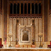 """Temple Emanu-El Ark <br><br> From a pdf file from the <a href=""""http://www.emanuelnyc.org/simple.php/about_tour"""">Temple Emanu-El website:</a>  <br><br> """"The single most important element within the sanctuary is the ark, which in Emanu-El's case houses seven Torah scrolls (seferei Torot). The ark doors are made of cast and hand-finished bronze in a pierced design with the Ten Commandments at the center. The Torah crowns situated on the upper Torahs of the ark are know as the Bloomingdale Crowns and were given to Congregation Beth-El by Lyman Bloomingdale (founder of the department store) in memory of his mother, brother and daughter in 1891 when the members of Beth-El dedicated their former home at 76th Street and Fifth Avenue. The perpetual light (ner tamid) suspended over the ark is enclosed in ruby glass set in bronze and was executed by Edward F. Caldwell & Company. The frame of the ark opening is crafted in Siena marble with mosaic inserts. Decorative metalwork at the top of the ark was executed by the General Bronze Corporation. The columns of the ark are made of French Benou Jaume marble, which varies in color from deep purple to orange."""" <br><br> """"The menorahs that flank the ark are seven-branched lamp stands, representing those that were used in the Tabernacle. The menorahs were produced by Edward F. Caldwell & Company. The enamel embellishments at the base were executed by the master metalworker and artist Oscar Bach."""""""