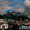 Mount Marathon and the Kenai Mountains and blue skies and swirling black clouds frame busy Seward Harbor at Holiday Inn Express on Resurrection Bay within Seward and the Kenai Peninsula (USA Alaska Seward)