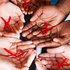 group of multiracial people holding red ribbon with both hands