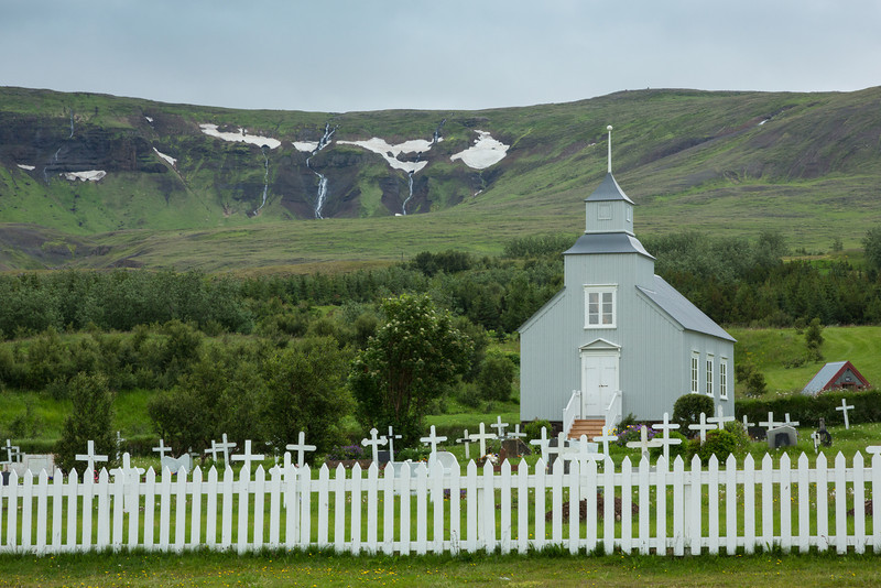 A small church and cemetery in the village of Hvammstangi, Northwest Iceland. A fresh grave can be seen in the cemetery, with waterfalls in the background.
