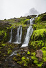 A set of waterfalls with mossy rock. Taken on the Norðfjall Peninsula, Westfjords, Iceland.