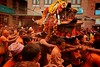 During Sindur Jatra devotees throw orange powder and roam Thimi village carring palanquins with local gods