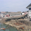 A boat carried to shore and left in the rubble from the 2004 Boxing Day Tsunami in Aceh Province, 2005.
