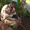 An old man sits in a stump in a rural community on the island of La Gonave.