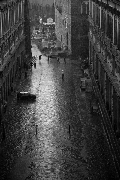 Looking out from the Uffizi Gallery, in the rain. A copy of Michelangelo's statue of David in the Palazzo Vecchio, in the distance. Florence, Italy