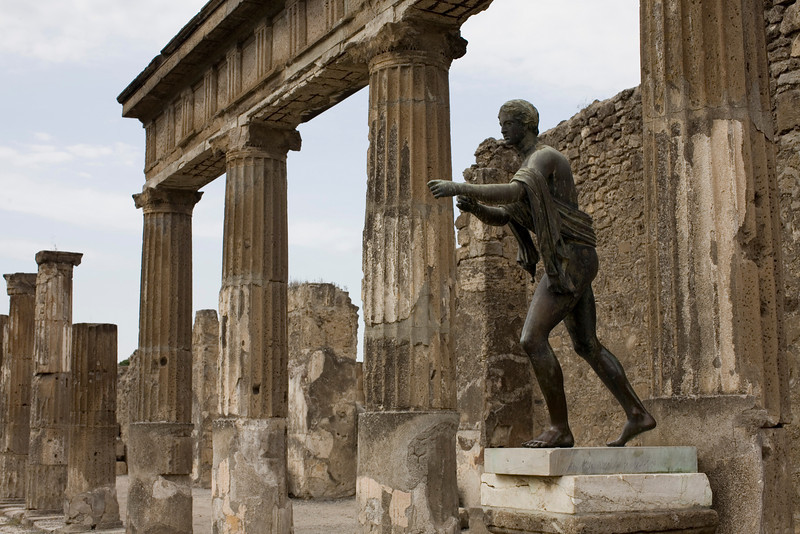A bronze statue of a god the great court of the Temple of Apollo pulling back his bowstring.  Pompeii, Italy.