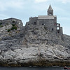 Fishermen pass by San Pietro Church, started in early Roman times and finished in the 13th century, in the town of Portovenere, on the Ligurian coast of Italy
