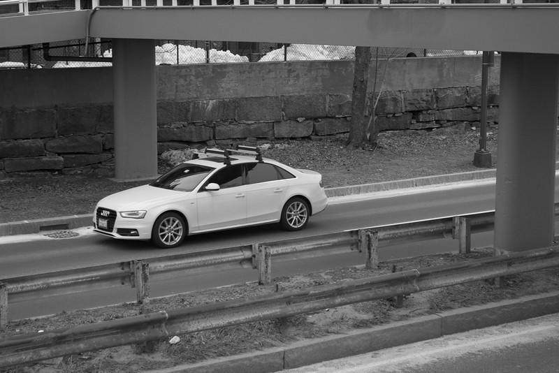 A white Audi driving down Storrow Drive in Boston, Mass. on a winter afternoon in March. Photo by Amanda Lake.