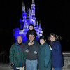 family in front of Cinderella's Castle at night