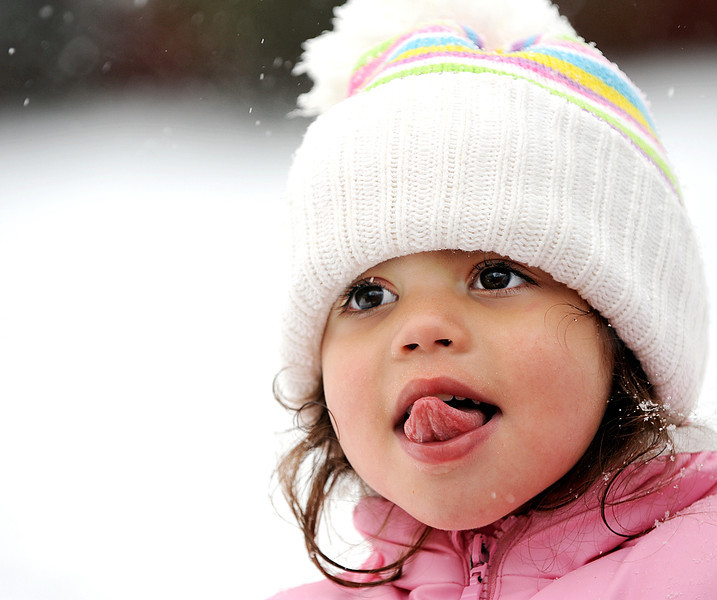 Chloe Roldan, 3, of Summer Street in Auburn, tastes snowflakes as they fall while walking down Whitney Street with her father.