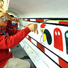 "James Bellamy, of Elyria, pulls off the tape on a pacman design snow plow blade for ""Beautify the Blades"" project at Lorain County JVS on Oct. 24.    Steve Manheim"