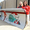 "Mary Beckett, left, of Amherst, and Heather Sump, of Elyria, both web and graphic design students, stand with their Grinch plow design on a snow plow blade for ""Beautify the Blades"" project at Lorain County JVS on Oct. 24.    Steve Manheim"