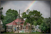 Image of old Carnegie stone library in Charlotte, Michigan with a rainbow overhead. Image taken summer of 2013.
