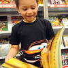 Anthony Pulley, a first grader at Franklin Elementary, browses through books at a student preview for the Scholastic Book Fair on April 7. STEVE MANHEIM/CHRONICLE