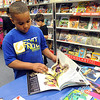 Alex Sanchez, a first-grader at Franklin Elementary, browses through books at a student preview for the Scholastic Book Fair on April 7. The annual book fair is a fundraiser for classroom books and field trips. STEVE MANHEIM/CHRONICLE