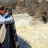Amie Dunstan and her great-nephew, Devyn Lear, 5, of Elyria, check out the high water level at East Falls Riverwalk on April 8.   STEVE MANHEIM/CHRONICLE
