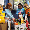 Faith Schneider, left, Nina Chatmon and Joseph Young, second graders at Liberty Elementary in North Ridgeville, place donations in boxes for the Liberty Sutdent Council's dog and cat food drive on Jan. 22.  The drive continues through Friday, with donations going to Lorain County APL.   Steve Manheim