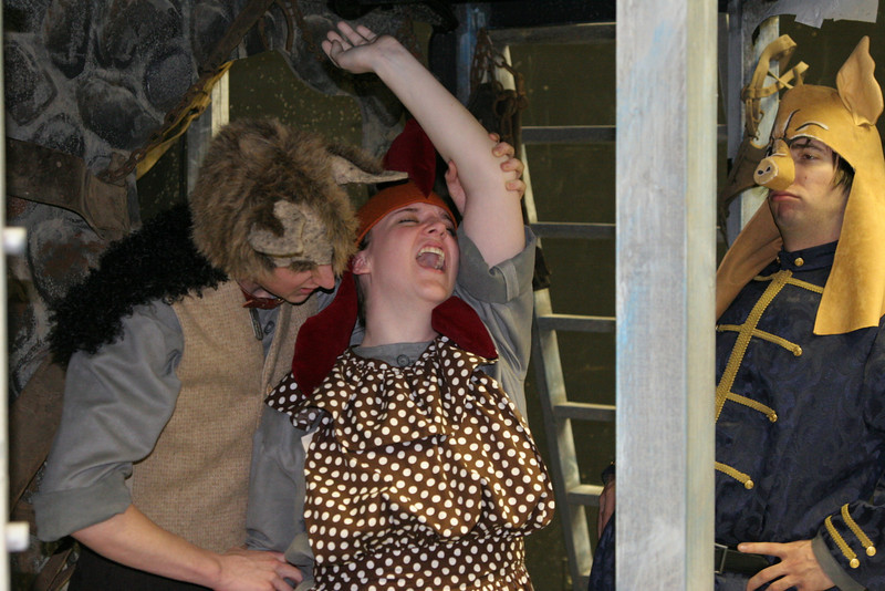 From left  Tyler Elliott, the Guard Dog, tortures Jenn Weitzel, the Hen as Joey Gambetta, Minimus the Pig Poet watches. This is a scene from Animal Farm which is being performed in the Larry Wismer Theatre.