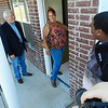 Staff photo by Dylan Goforth<br /> Cherokee Nation Chief Bill John Baker watches as Tia Sallis enters her new home for the first time Thursday in Fort Gibson. Sallis and her two sons were one of seven families to receive keys this month for new homes built by the Cherokee Nation's Housing Authority.