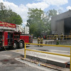 Newtown Hook & Ladder's aerial ladder truck is posted at the town's waste transfer station off Ethan Allen Road on May 12 where all five local fire companies responded to put out a fire within a garbage storage building.   (Hicks photo)