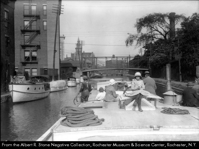 """Title: Boat ride on the canal [photograph]. <br /> Photographer/Artist: Stone, Albert R., 1866-1934.<br /> Date: 1915?<br /> Physical Details: 1 photograph : b&w ; 7 x 9 in.<br /> Collection: Albert R. Stone Negative Collection, Rochester Museum & Science Center, Rochester, NY<br /> Summary: Three men, a woman, and two children take a boat down the canal in downtown Rochester. Several other boats are docked along the edges of the canal.<br /> Notes: Printed in Rochester Herald, June 13, 1915. <br /> Rochester Images image Number: sct08942 <br /> <br /> <a href=""""http://www.rochester.lib.ny.us/rochimag/rmsc/"""">http://www.rochester.lib.ny.us/rochimag/rmsc/</a><br /> scm08/scm08942.jpg"""