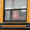 SAM HOUSEHOLDER   THE GOSHEN NEWS<br /> Fourth grader Regina Yoder looks out the bus window Tuesday at Shipshewana Scott Elementary School. Tuesday was the first day of class for the 2014-2015 school year.