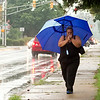 SAM HOUSEHOLDER | THE GOSHEN NEWS<br /> Dawn Stanback, Elkhart, lights a cigarette while walking beneath her umbrella down Monroe Street in Goshen Tuesday. Afternoon rain made for a wet commute for people getting off of work and school.