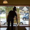 SAM HOUSEHOLDER | THE GOSHEN NEWS<br /> Subway manager Cristina Hall cleans around a window in the restaurant looking out over Pike Street Wednesday in Goshen. The restaurant sits close to the road which has a proposal to be widened and would require the restaurant to be moved.