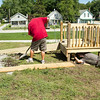 SAM HOUSEHOLDER | THE GOSHEN NEWS<br /> Goshen Parks Department emplouyees, from left, Ron Suggs, Roger Taylor and Kevin Yoder work on building a handicap accessible platform at the new Mill Street Park Wednesday. The park is on the former Quality Drive-Away site.