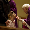 SAM HOUSEHOLDER | THE GOSHEN NEWS<br /> Vivina Andrews, 4, of Nappanee, gets ashes on her forehead during a service at St. John the Evangelist Catholic Church Wednesday. Ash Wednesday begins the Lenten season in many Christian faiths.