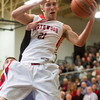 SAM HOUSEHOLDER | THE GOSHEN NEWS<br /> NorthWood senior Jonathan Wilkinson grabs a rebound against Lakeland Wednesday during the 3A Sectional game at Wawasee.