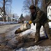 SAM HOUSEHOLDER | THE GOSHEN NEWS<br /> Nick Hornish of the Goshen Water and Sewer Department dumps a bucket of muddy water onto Wilden Avenue while helping fix a water line leak Thursday. Wilden Avenue between Main and Third streets was closed for a few hours while the work was being done.