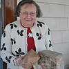"Margot Hall holds two thick ""klinkers,"" fired clay bricks, salvaged from the site of her birthplace in prewar Forst-Berge, Germany. One has marked her entryway since she brought it back to America in 1991, the other joining it after her mother's death in 2002. (Crevier photo)"