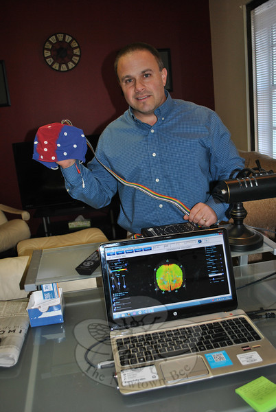 "Jeff Schutz of Western Connecticut Center for Neurofeedback and Counseling displays the simple equipment needed for neurofeedback therapy. A ""beanie"" cap has wires that plug into an amplifier, which in turn is plugged into a computer displaying the brain. The display shows Mr Schutz areas of brain activity as the client watches television. (Crevier photo)"