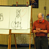 Former resident and renowned children's book illustrator and author Steven Kellogg gave a presentation for Sandy Hook Elementary School students on Thursday, January 16. During the presentation, he drew images of his former pets and characters, Pinkerton, right, and Rose, left. He also held his hands together to demonstrate how small Rose was when she first came to live with his family. Award-winning author Patricia MacLachlan also visited the school during the day. (Hallabeck photo)