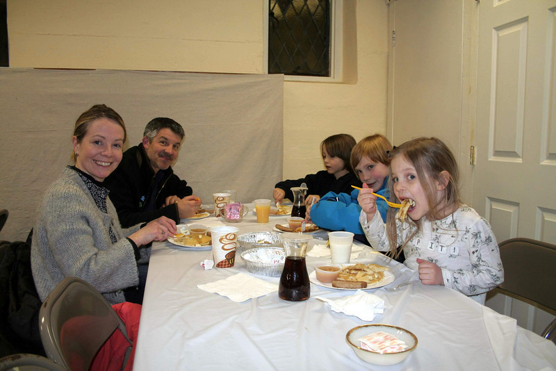 "Neasa Waaler, foreground, and Ian Hockley, behind her, took their children to the 57th Annual Shrove Tuesday Pancake Supper at St John's Church on March 7. The friends were among those who dined on pancakes, country-style sausage, and applesauce in the undercroft of the Sandy Hook church. Approximately 60 dinners were served this year before a water problem caused an early close to the yearly event. Dozens of people had to be turned away after 6 pm, said St John's member Cheryl Moulthrop, because the volunteers did not have water to work with any longer. ""We were disappointed we had to turn people away, but we didn't have a choice,"" she said Wednesday morning. Due to a shortage of volunteers this year, there wasn't time to do the homemade corned beef hash that has long been part of the meal. ""There was some disappointment over that, too,"" said Mrs Moulthrop, ""but it was still a great meal."" Jake, Aidan and Teagan, the children dining with Ms Waaler and Mr Hockley, certainly looked like they were enjoying their dinner. (Hicks photo)"