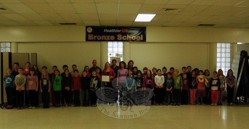Middle Gate Elementary School students stood with, center from left, physical education teacher Tony Sortino, Chartwells School Dining Services Resident Dietitian Jill Patterson, nutrition staff member Suellen Braddock, physical education teacher Laura Cooper, and nutrition staff member Diane Fisher for a photo to commemorate all Newtown Elementary Schools earning HealthierUS School Challenge recognition. (Hallabeck photo)