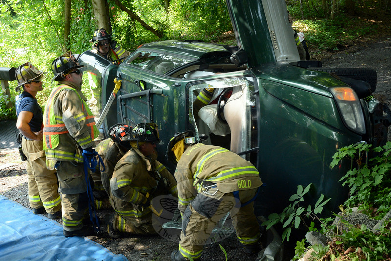 Volunteer firefighters from Hawleyville and Hook & Ladder joined forces late on the morning of Friday, July 25, to extricate a woman from a station wagon that had flipped over onto its side, trapping her. Police said that motorist Flerida Garcia, 61, of Danbury was driving a 2000 Subaru Outback westward on Mt Pleasant Road at about 11:30 am, when she lost control of the auto, exited Mt Pleasant Road and then drove onto Sedor Lane, where the vehicle then struck a stone wall, causing it to flip over onto its right side. The Newtown Volunteer Ambulance Corps transported Garcia to Danbury Hospital on a report of pain, police said. The accident is under investigation, according to police. (Gorosko photo)