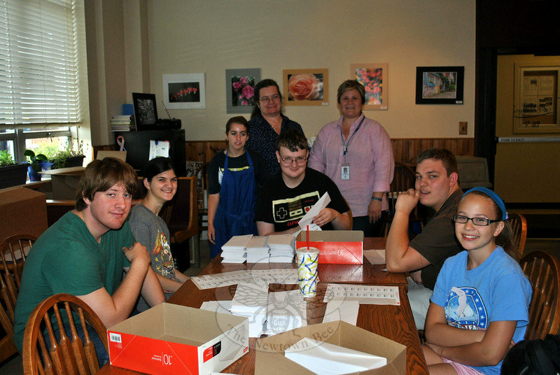 Student volunteers and students from the Vocational Extended School Year Program address envelopes for the Outreach Committee of the Commission on Aging, Thursday morning, July 31, at LeReine's Cuisine, 30 Pecks Lane. The students spent Monday through Thursday mornings, the weeks of July 21 and 28, placing SASE inside each envelope containing a survey for Newtown residents ages 60 to 95, and placing address stickers on each one. From left are Ryan Gray, Danielle Mola, Brandi Braziel (standing), LeReine Frampton, outreach committee member and owner of LeReine's Cuisine, VESY teacher Noel Macfadyen, Paul Jeffrey, Matt Knapp, and Lilly Macfadyen. (Crevier photo)